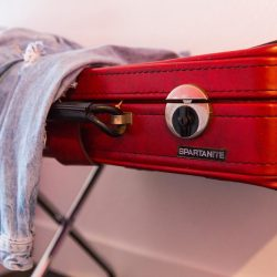 Rambler: Red leather suitcase with jean jacket hanging on it