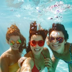 Rambler:Cheerful women friends swimming underwater in pool taking selfie. Underwater selfie of happy females in pool.