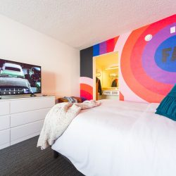 Rambler: view of one queen bed with RAD wall graphic and TV in view