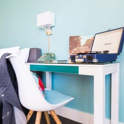 Rambler: desk with blue record player on it and chair with leather jacket draped over it