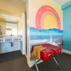 Rambler: view of room sink and red leather suitcase in front of Here Comes the Sun wall graphic