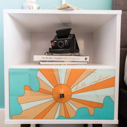 Rambler: view of nightstand with graphic on it and books and camera on it