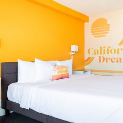 View of bed with California Dreamin artwork on the wall