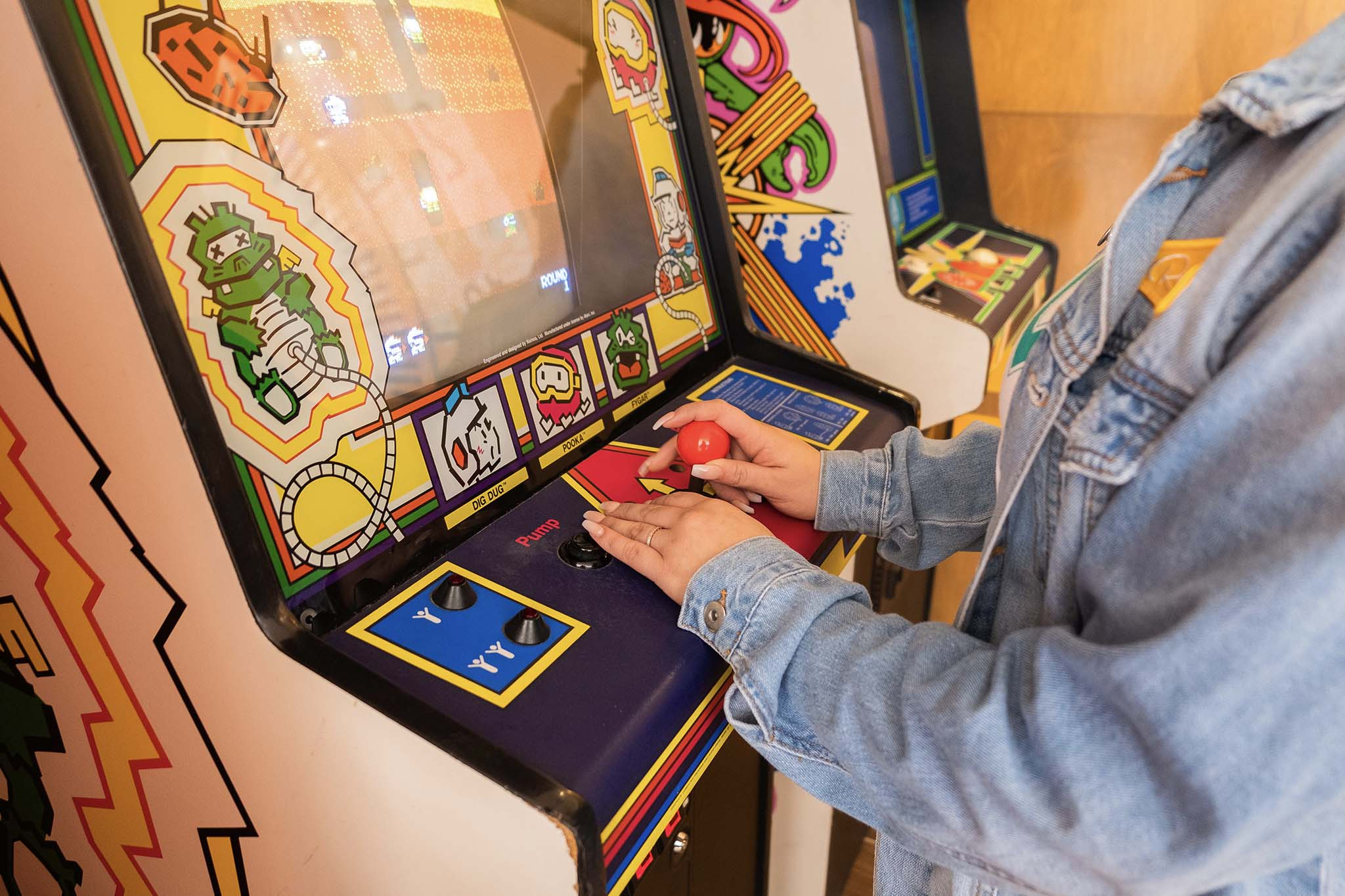 View of hands of a girl wearing a demin jacket playing an old school arcade game