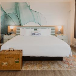Bed in Rambler suite with Dreamer pillow and blue water color graphic behind the headboard