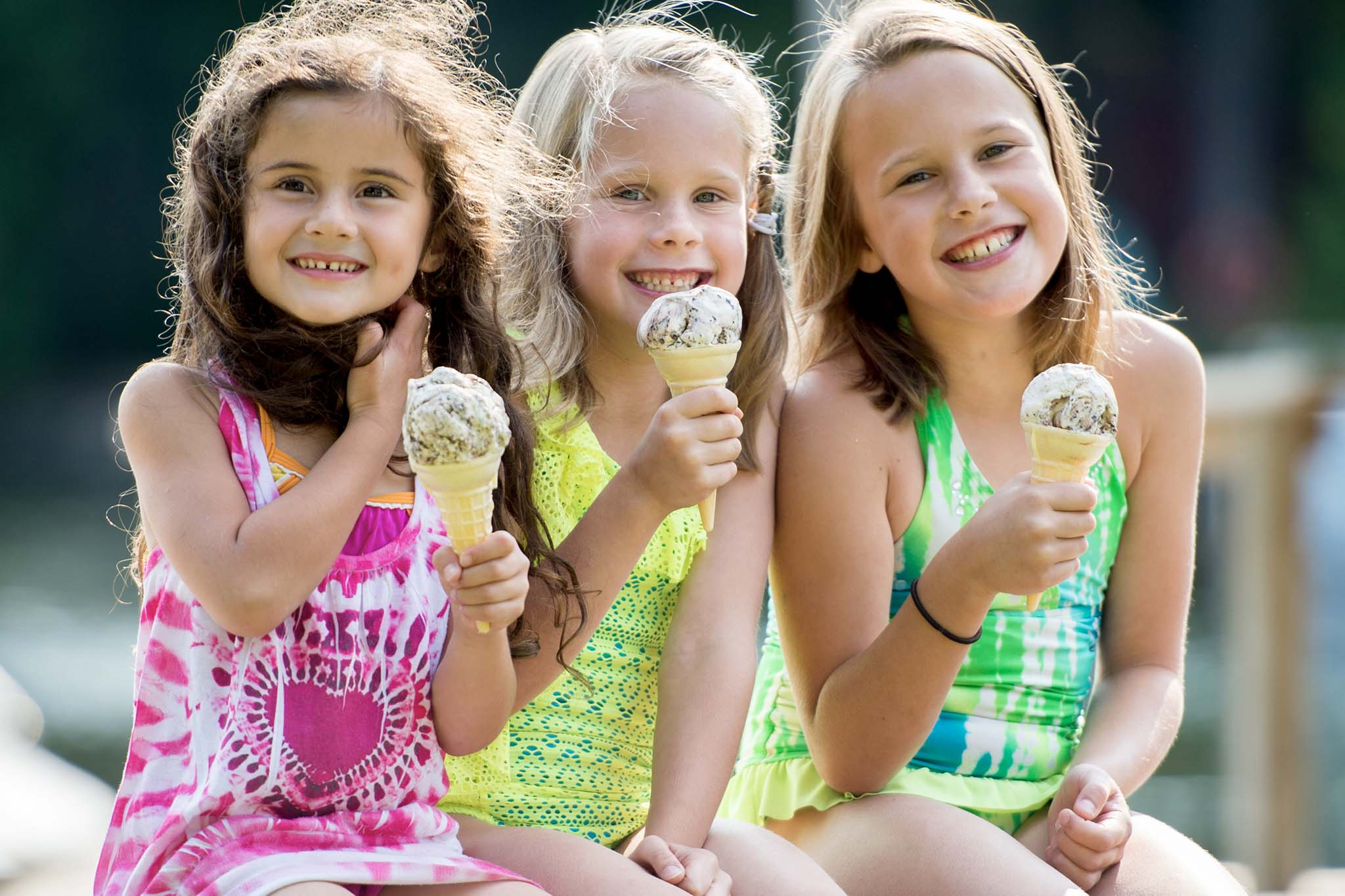 3 young girls eating ice cream at the pool