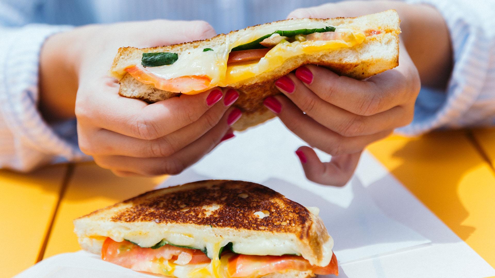 Hand pulling apart a cheesy sandwich