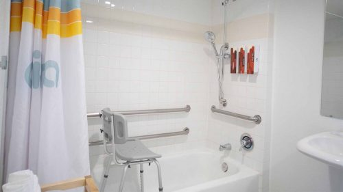 Chair and hand rails in ADA accessible bath tub