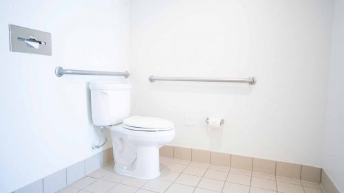 Toliet in ADA bathroom with hand rails next to it