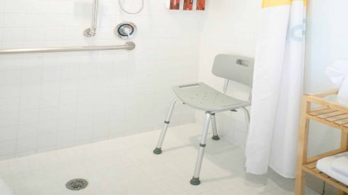 Chair and wall handle rails in ADA accessible walk in shower