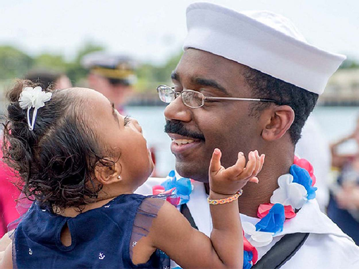 Navy father holding his daughter sweetly looking into each other's eyes