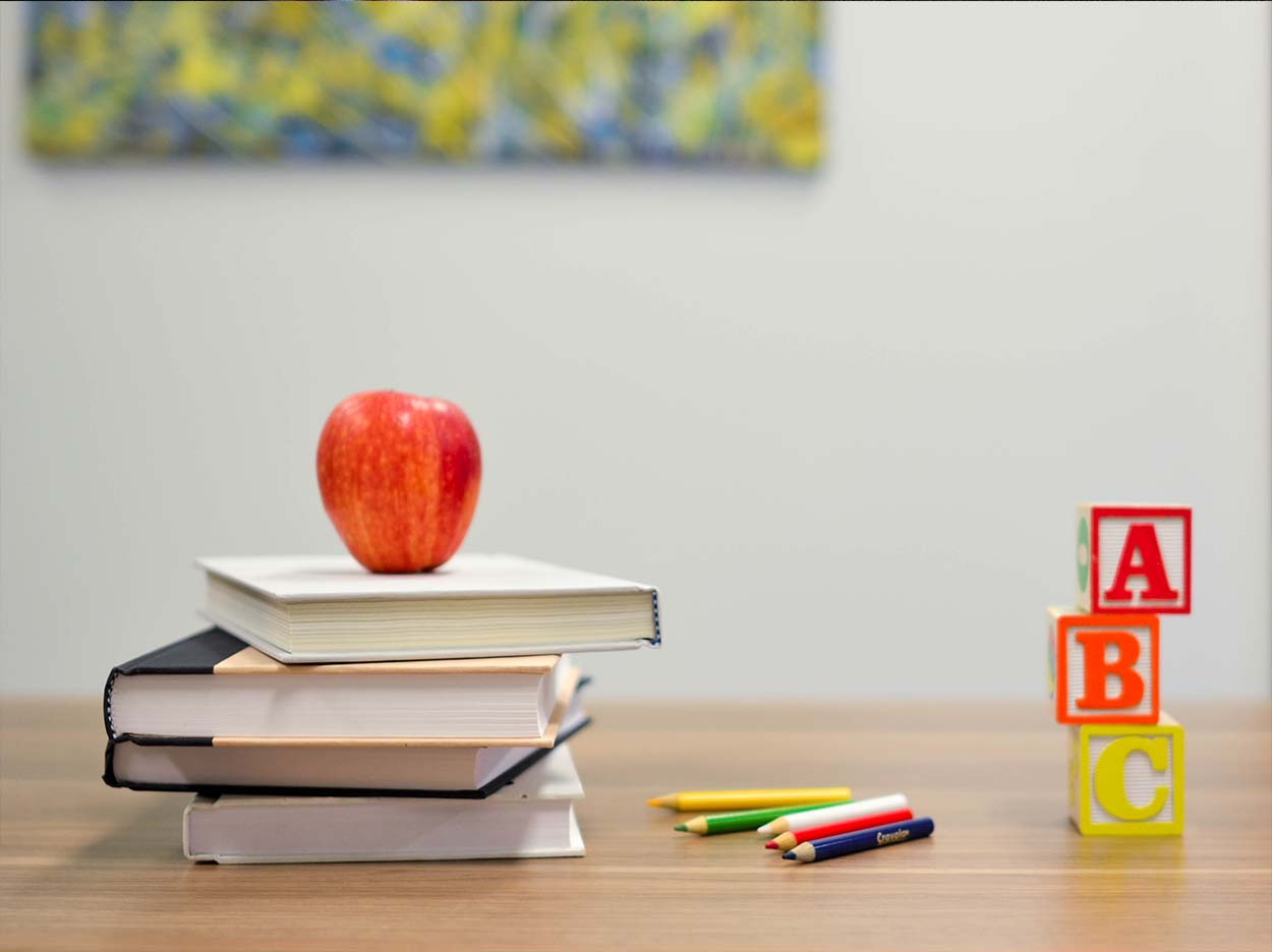 Stack of books with apple on top. Colored pencils and stack of blocks that says A B C.